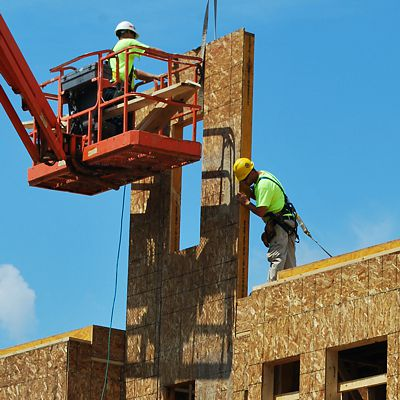 Aerial lift on jobsite with workman placing a wall panel that has been lifted by crane