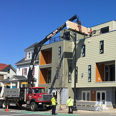 National Lumber boom truck delivery of drywall directly into upper floor of building.