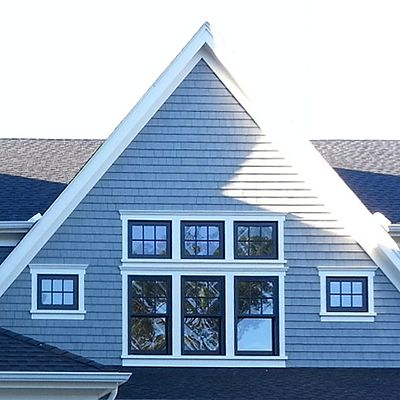 Golden Development custom home with blue-gray siding, closeup of upstairs windows