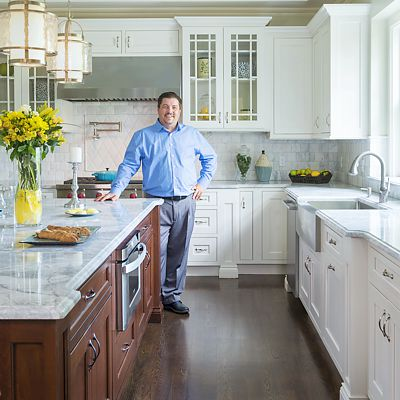 Designer Ed Nunes in a kitchen he designed for a home in Chestnut Hill