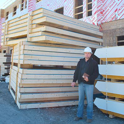 Panelized wall panels and stair stringers are examined on the jobsite by a National Lumber worker