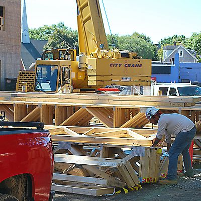 Prefabricated floor trusses are prepared by worker for crane to lift